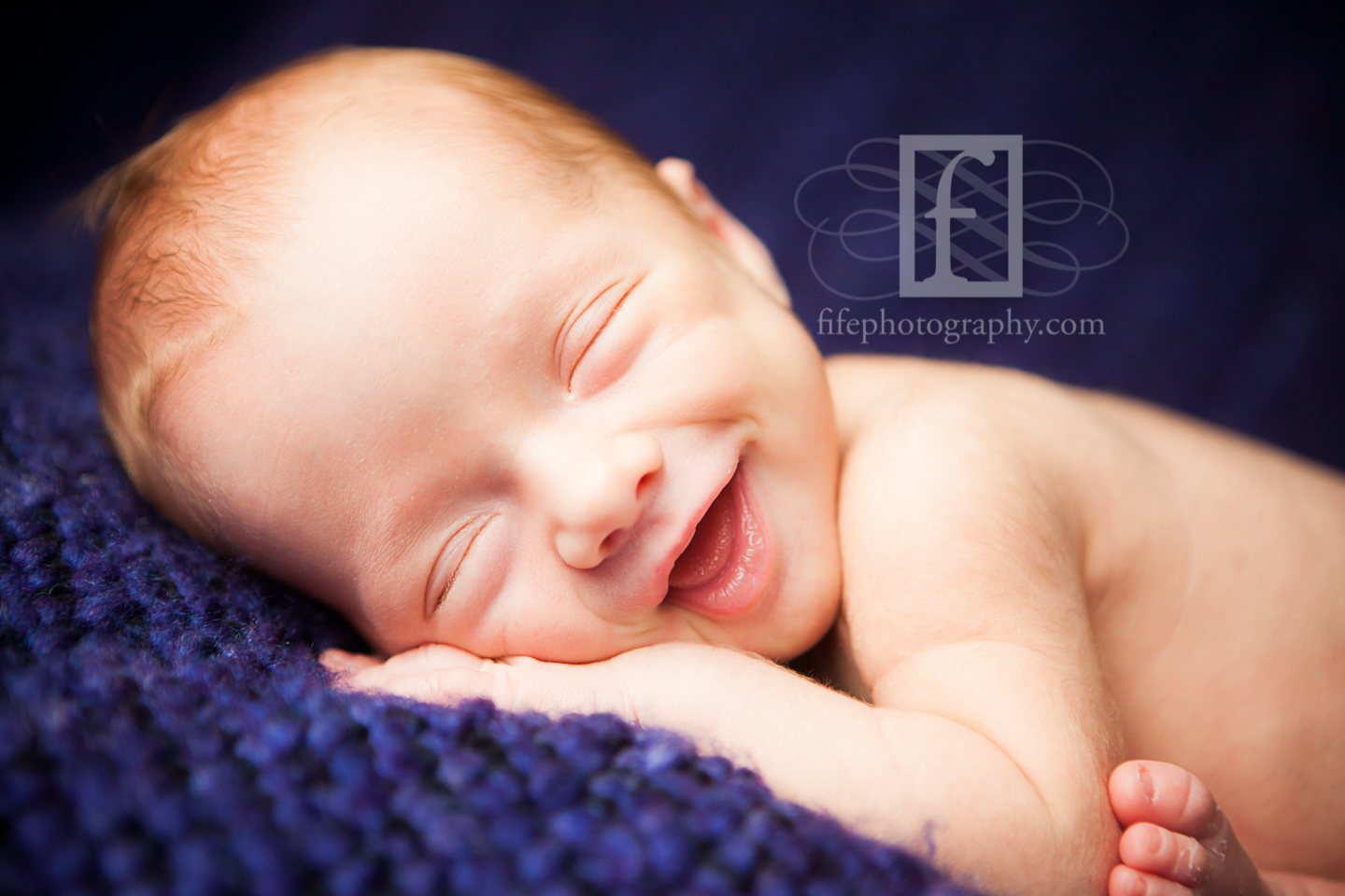 newborn baby smiling on blue blanket