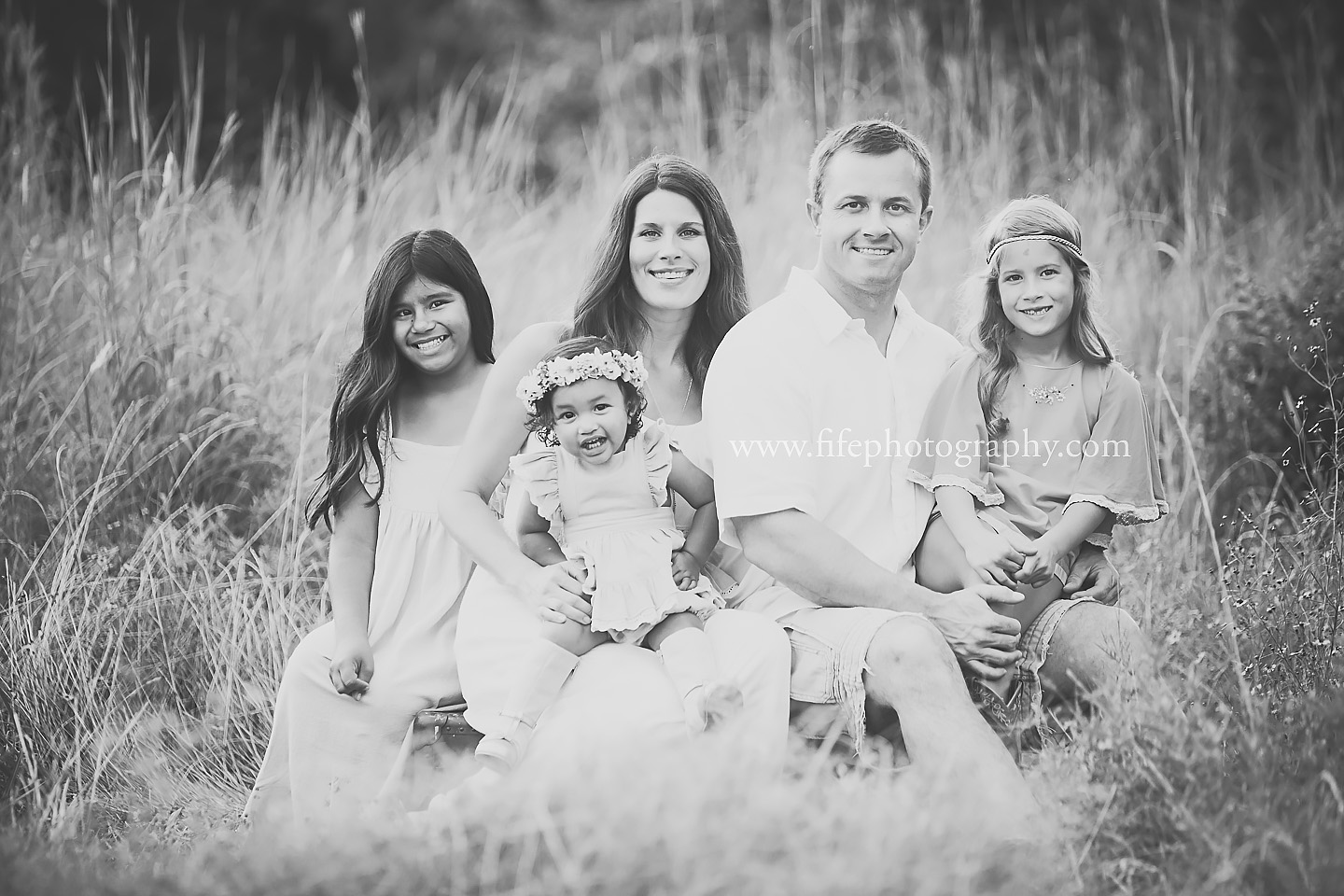Smiling Family sitting in tall grasses