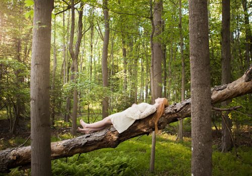High school senior wearing white dress laying on fallen tree in south jersey woods